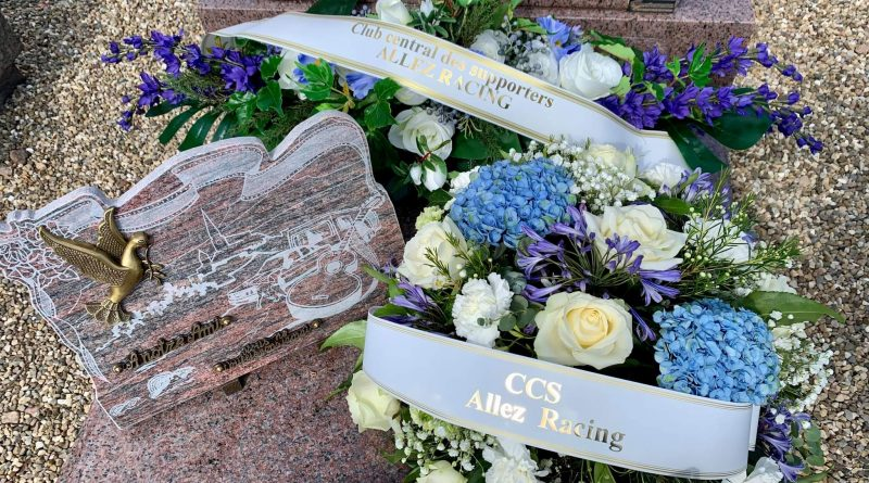 Sur la photo d'illustration, en fond, la gerbe florale avec des fleurs artificielles ; sur le coté gauche, la plaque du conseil d'administration ; sur le côté droit, la composition florale avec des fleurs naturelles.
